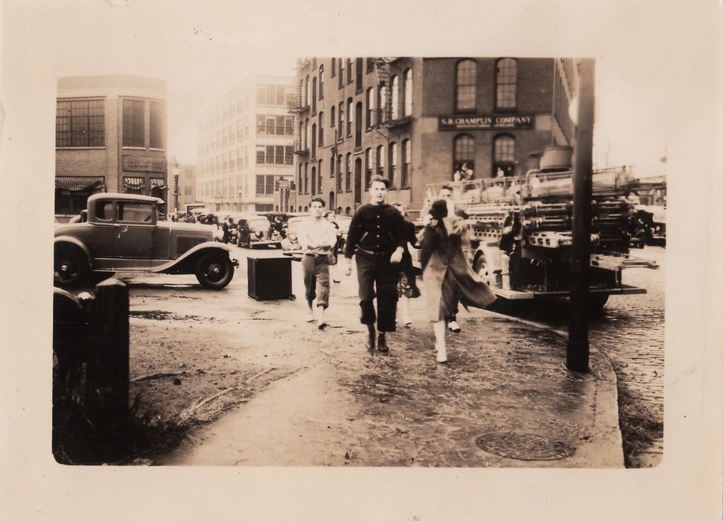 Walking down Ship Street after the waters receded. Men have their trousers rolled up to navigate areas of standing water. New England Hurricane of 1938. Providnece, Rhode Island, September 22, 1938.